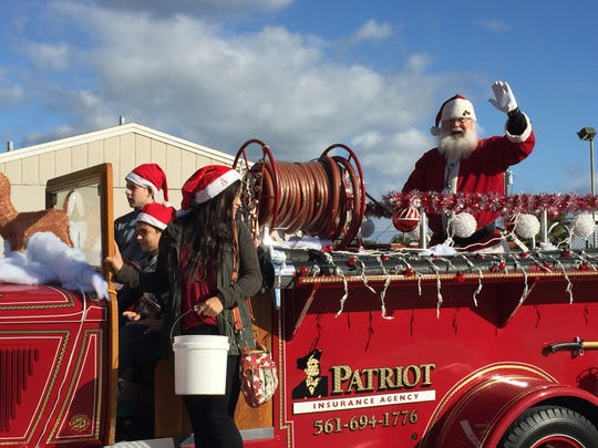 Santa, atop a fire engine, delights kiddies along the parade route. And just about everyone was on their feet.