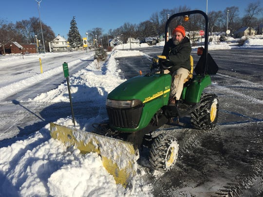 Don Wallace uses a small tractor to clear the walks at St. Clair County Community College. Classes were to resume at noon Thursday.