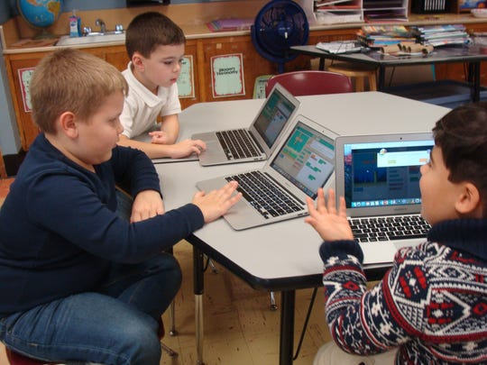 First-graders in the Linden Gifted and Talented program, which draws students from the school district's eight elementary schools, program custom versions of the game Flappy Bird as part of their Hour of Code. From left are Dominick Skwirz of School No. 6, Raymond Benkovich of School No. 10, and Tiago Jimenez of School No. 1.