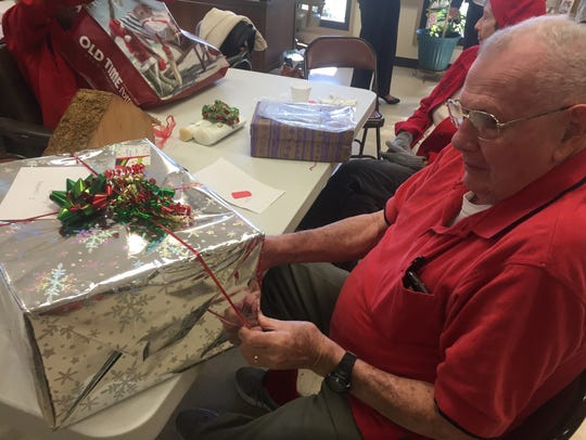 During a party at Martin Andersen Senior Center, Francis Stafford opens a gift provided through the Reaching Out Holiday Fund campaign. Stafford's wife of 66 years, Pauline Stafford, died in September 2017.