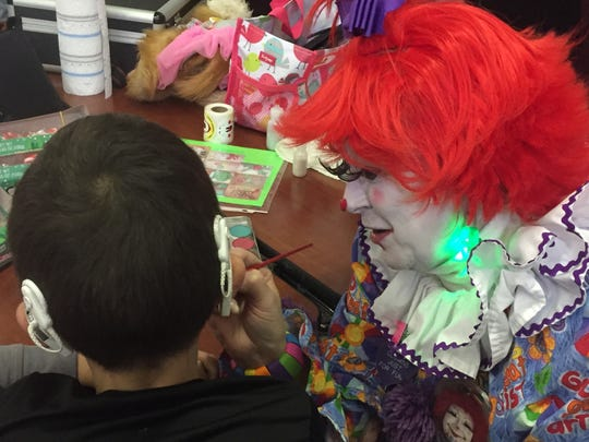 Gabbie the Clown paints a little Christmas cheer on Javier Valdez' cheek.