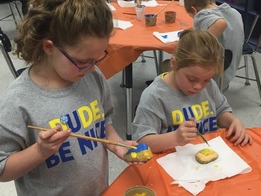 Mykaila Carpenter and Barbie Davis, second graders at Roseville Elementary, paint kindness rocks that will be distributed throughout the community by high school students.