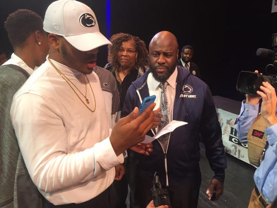 Micah Parsons talks to coach James Franklin as he looks over his signed letter-of-intent to attend Penn State and play football for the Nittany Lions. He's pictured next to his father, Terrence, a long-time Penn State fan.