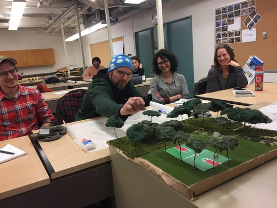 Jon Adams-Koliltz, planning coordinator with Burlington Department of Parks, Recreation and Waterfront, critiques a model created by UVM student Andrew Kenney for Baird Park during an end-of semester presentation on Dec. 7, 2017. He is joined by his colleagues, from left: Max Madalinski, Nina Safavi and Diana Wood.