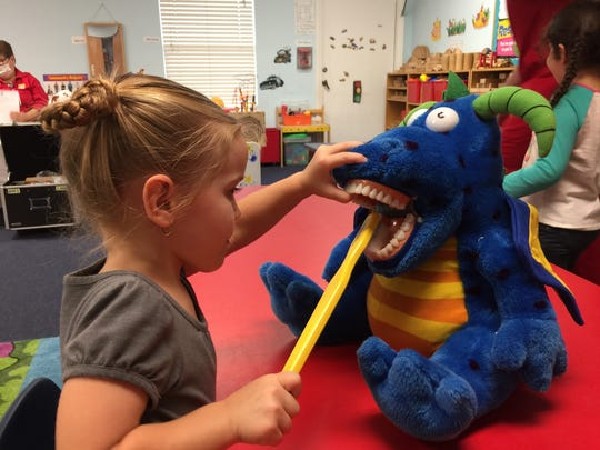 A child from the Gertrude Walden Childcare Center demonstrates good tooth brushing on the Dental Dragon!