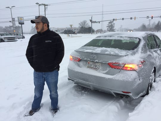 Karlo Paver of Iowa stands behind his rented Toyota Camera on Thursday morning after the car got stuck in the snow on Naylor Mill Road, just east of North Salisbury Boulevard.