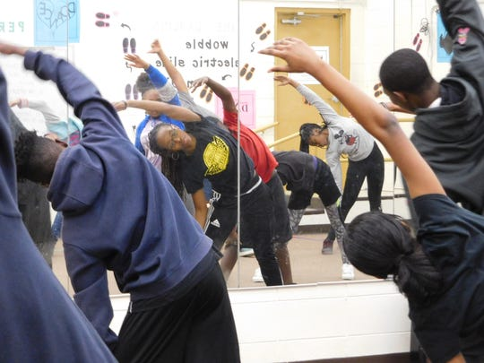 Kelsey Boyer leads her dance students in stretching exercises.
