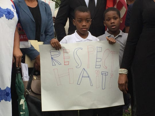 A boy holds a sign in the Little Haiti neighborhood