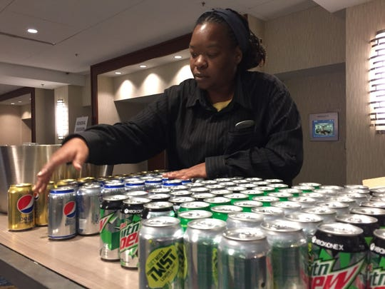 Jamese Gibbs, a banquet server at the Hyatt Regency in downtown Greenville, refreshes beverages for the TCI Tires conference on Wednesday. It was business as usual at the hotel despite snowy conditions outside.