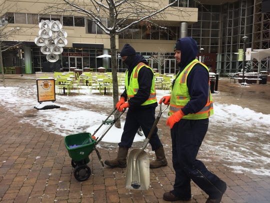 Greenville Public Works crew members Tavarus Inabinet, left, and Justin Chapell use salt and shovels Wednesday to keep sidewalks in downtown Greenville free of ice.