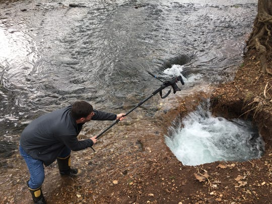 A week before the city fenced off the site, News-Leader photographer Drew Jansen carefully took a photo of the larger swallow hole on Wilson's Creek.