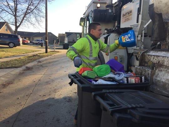 Lafayette truck driver Bryan Roberts throws a few recyclables into the truck before it dumps.