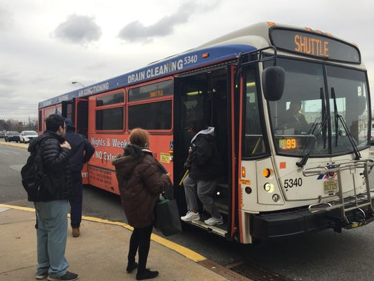PATCO passengers board a free shuttle bus ferrying between Ferry and Broadway stations on Monday. PATCO service was stopped after a Conrail train struck a pole along a rail line.