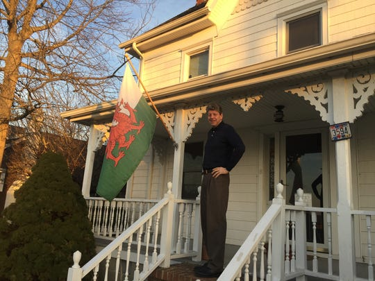 Artist Dan Thomas poses with the Welsh flag outside