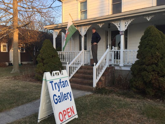 Artist Dan Thomas poses with the Welsh flag outside Tryfan Gallery in Chincoteague, Va.