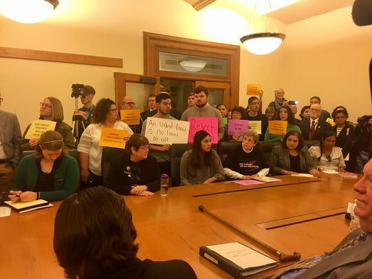 Members of the public hold signs in opposition to Senate File 481, which seeks to ban so-called sanctuary cities in Iowa.