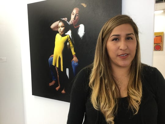 Adriana Flores with the portrait she painted of herself