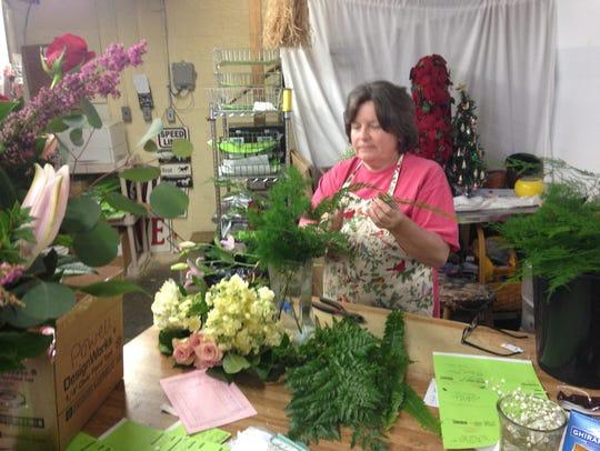 Floral designer Brenda Haun puts together an order.