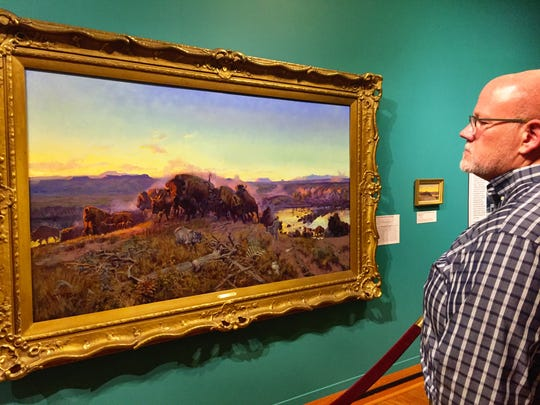 "CM Russell's ""When the Land Belonged to God"" painting is a strong contender for best object in the collection.Kirby Lambert, outreach and interpretation program manager, checks it out in the Russell exhibit at the Montana Historical Society in Helena."