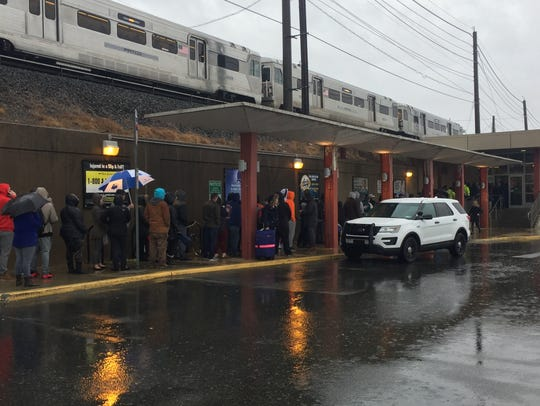 Eagle fans line up Wednesday in the rain outside PATCO's