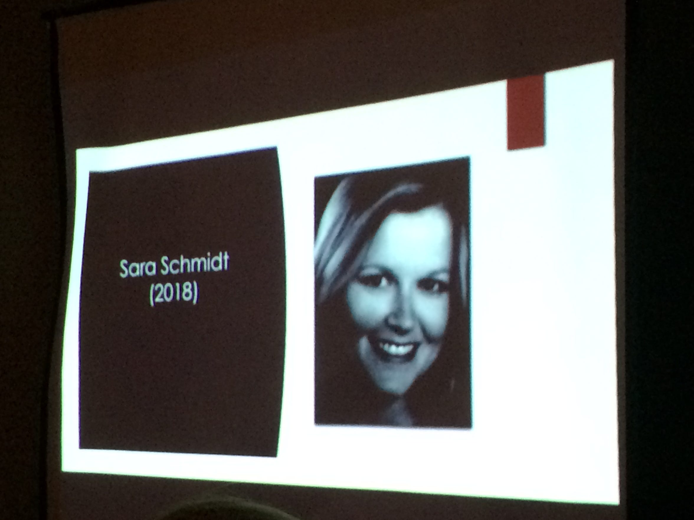 A slideshow shows an image of Sara Schmidt at a vigil. Schmidt died at the hands of her husband, Robert, in January.