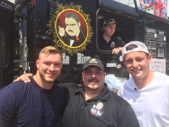 Nicholas Terzella (center), the owner of the Southern Tier Cheesesteak Co., with Washington Redskins Will Compton (left) and Tress Way (right).
