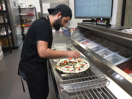 Sabri Arslankara, co-owner of Pizzava, a Midtown Reno pizzeria that opened in January 2018, builds a pie the other morning.