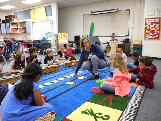 636541120572398476-Barbara-Hartsfield-shows-students-how-to-use-the-staff-in-the-center-of-the-music-rug.JPG