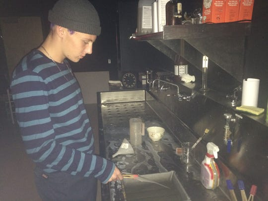 Tyler Gacek develops a photo in the darkroom at Jupiter Community High School.