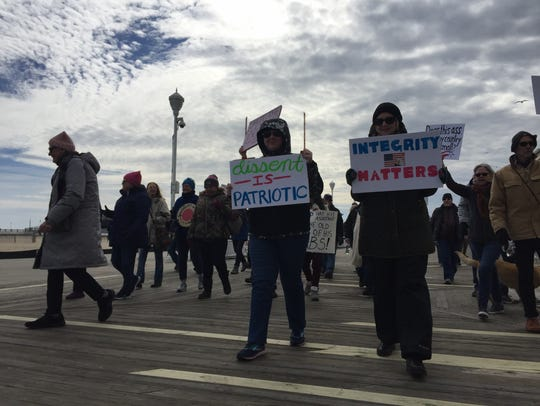 "About 75 protesters walk down the Ocean City Boardwalk on Saturday, Feb. 17, at a ""Not My President's Day"" march."