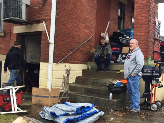 Jerry and Danny Campbell take a short break from the task of moving their parents' belongings from the family house on Union Street in New Richmond. They expect the basement to flood but not the living area.