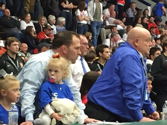 Catholic Central head coach Mitch Hancock (with his daughter) and assistant Bob Moreau wait for the final match to end.