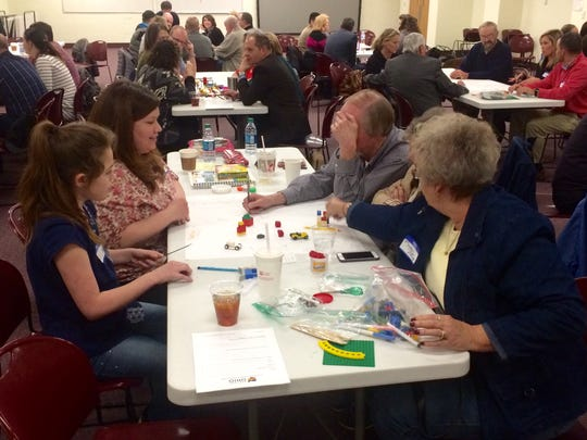 Attendees at Monday night's Main Street Ohio program work to create their ideal downtown using paper, markers and Lego bricks among other items.