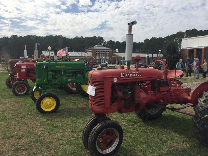 Vintage and antique tractors are displayed on the lawn