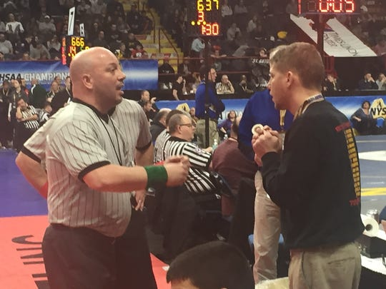 Bainbridge-Guilford/Afton/Harpursville coach Brandon MacNaught discusses a call with an official during last weekend's NYSPHSAA Wrestling Championships at Albany's Times Union Center.