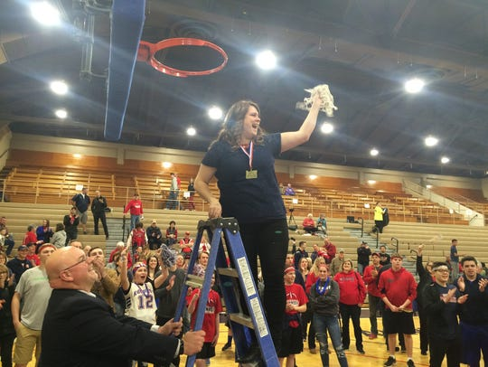 Kennedy co-head coach Kerry Hall holds the net after