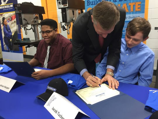 Michelin North America Chairman and President Scott Clark, center, signs 17-year-old Jacob Tucker's hiring papers for a first-of-its-kind high-school apprenticeship program that launched in Greenville this spring. Tucker is a junior at Mauldin High School. Sixteen-year-old Johnathan Harper, far left, is home-schooled and started his apprenticeship a month ago.