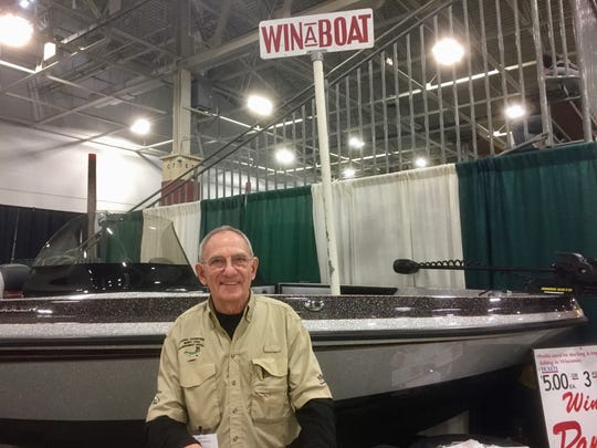 Sports show attendees can put their names in to win a boat, courtesy of the Musky Clubs Alliance of Wisc. Larry Slagoski staffs the booth.