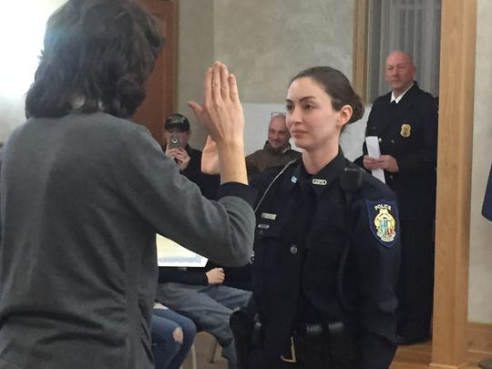 Officer Monica Clark is sworn-in as a Granville reserve police officer by Mayor Melissa Hartfield as Chief William Caskey looks on.