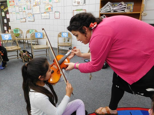 Aubrey Iacobelli helps a student with her finger placement.