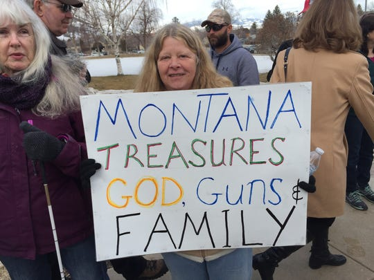 Kathy Cook of Helena says she was handed this sign as she entered Saturday's March for our Guns rally but agrees with its message.