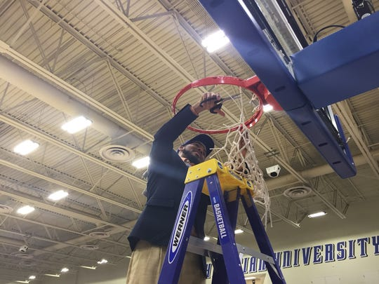TCC women's basketball coach Franqua Bedell cuts down the net following the Eagles' 69-51 win over Trinity Valley CC in Saturday's national title game.