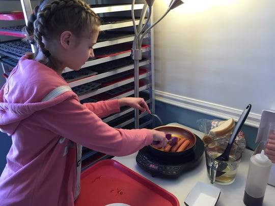 Julia Palmer, 13, prepares hot dogs Sunday at her family's