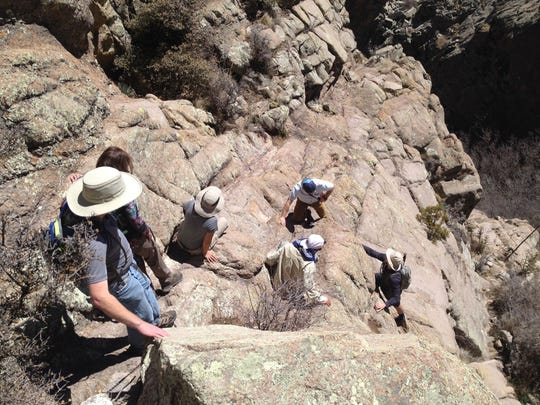 Members of the Jornada Hiking & Outdoors Club climb down the mountain side on a trip to Organ Needle.
