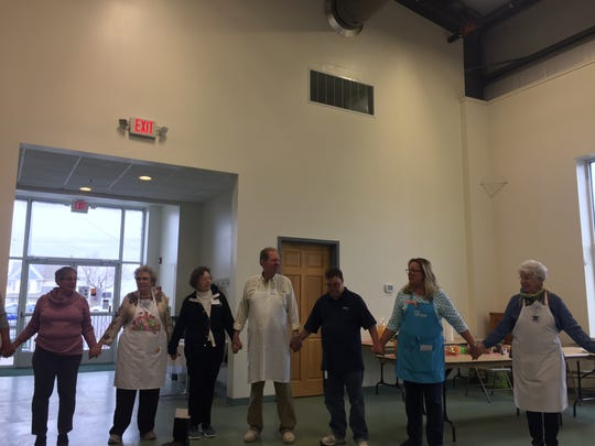 Volunteers at Manna Cafe join hands for a prayer before serving lunch at Christ United Methodist Church on Chincoteague, Virginia on Monday, March 26, 2018.