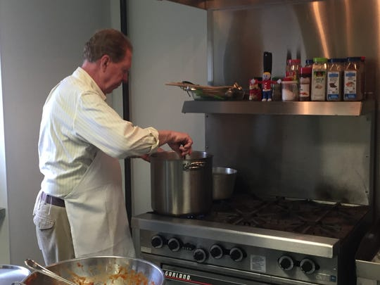 Bill Lytle stirs a pot of spaghetti sauce in the kitchen at Christ United Methodist Church on Chincoteague, Virginia on Monday, March 26, 2018.