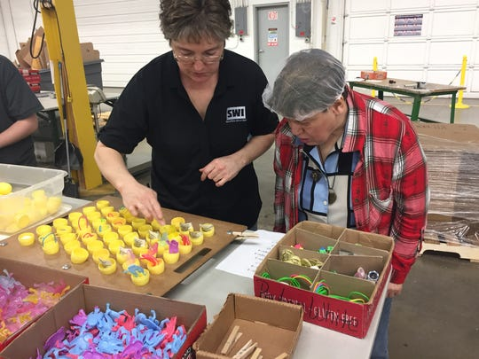Robin Murphy, Sunny Bunny production manager, checks the work of Becky Burgard, one of as many as 150 workers filling the eggs just in time for Easter.
