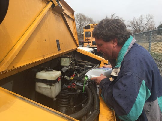 Steve Lesondak pours coolant into a bus engine that