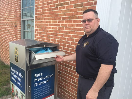 Capt. Todd Wessells demonstrates putting unwanted medicines in a drop box outside the Accomack County Sheriff's Office in Accomac, Virginia on Thursday, March 29, 2018.