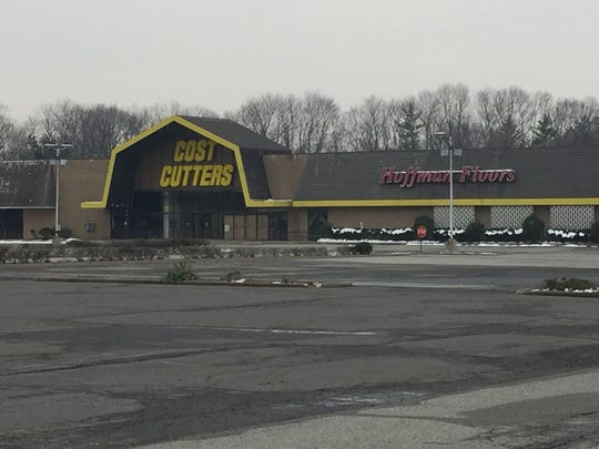 Remnants of a discount department store and flooring store make up the vacant building on the largely paved-over commercial tract.